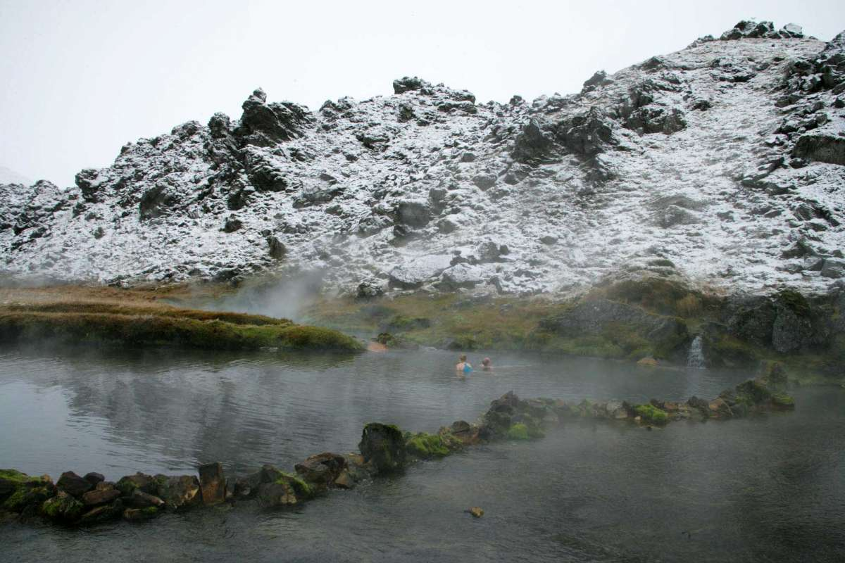 two persons swimming in hot spring during winter iceland