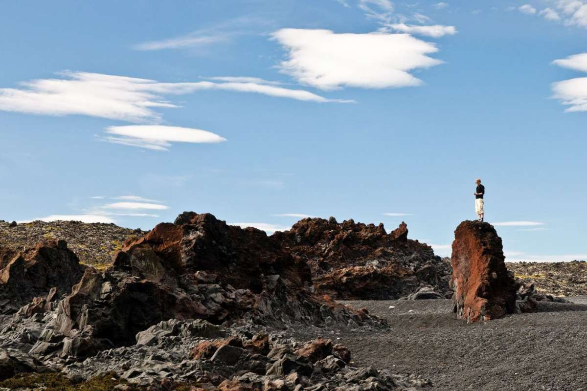 Man standing on rock at djupalonssandur, snaefelsnes peninsula, iceland