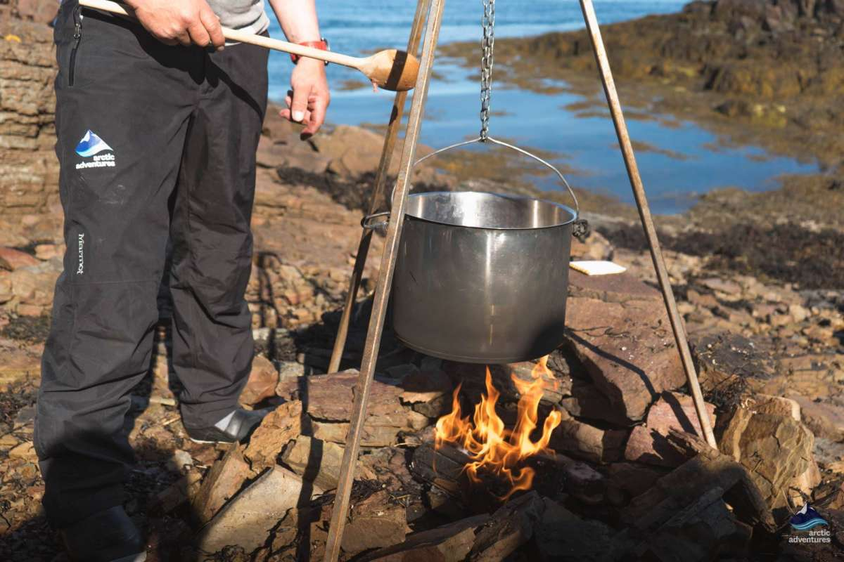 Man making food over open fire Iceland