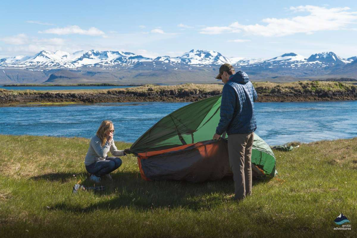 Two persons putting up a tent in Iceland