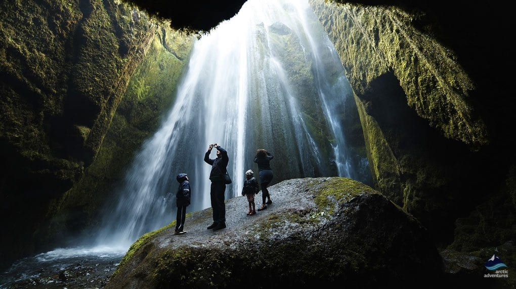 Family marveling Gljufrabui waterfall in Iceland