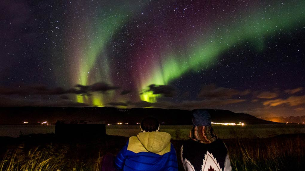 Couple watching the northern lights in the sky in Akureyri, Iceland