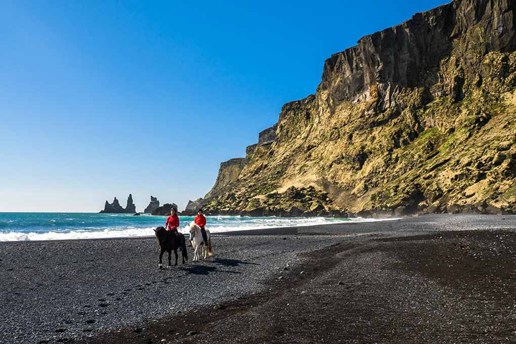 horse riding around black sand beach