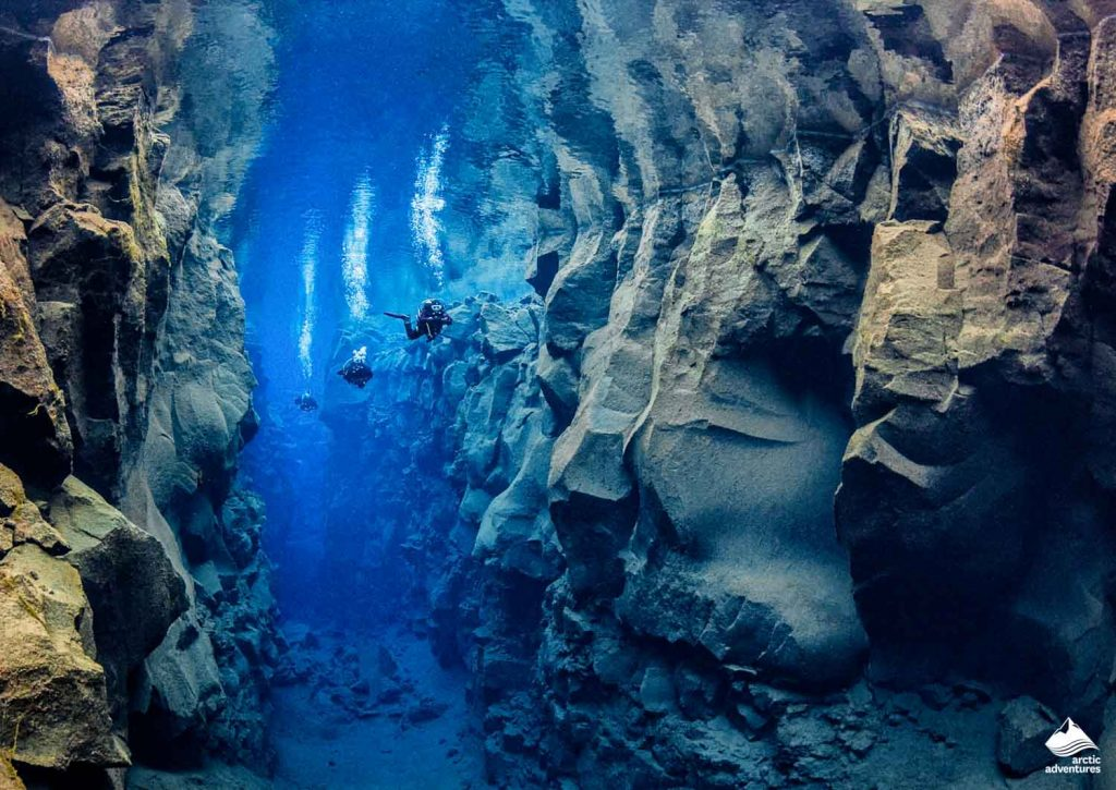 Divers diving in a row in Silfra Fissure