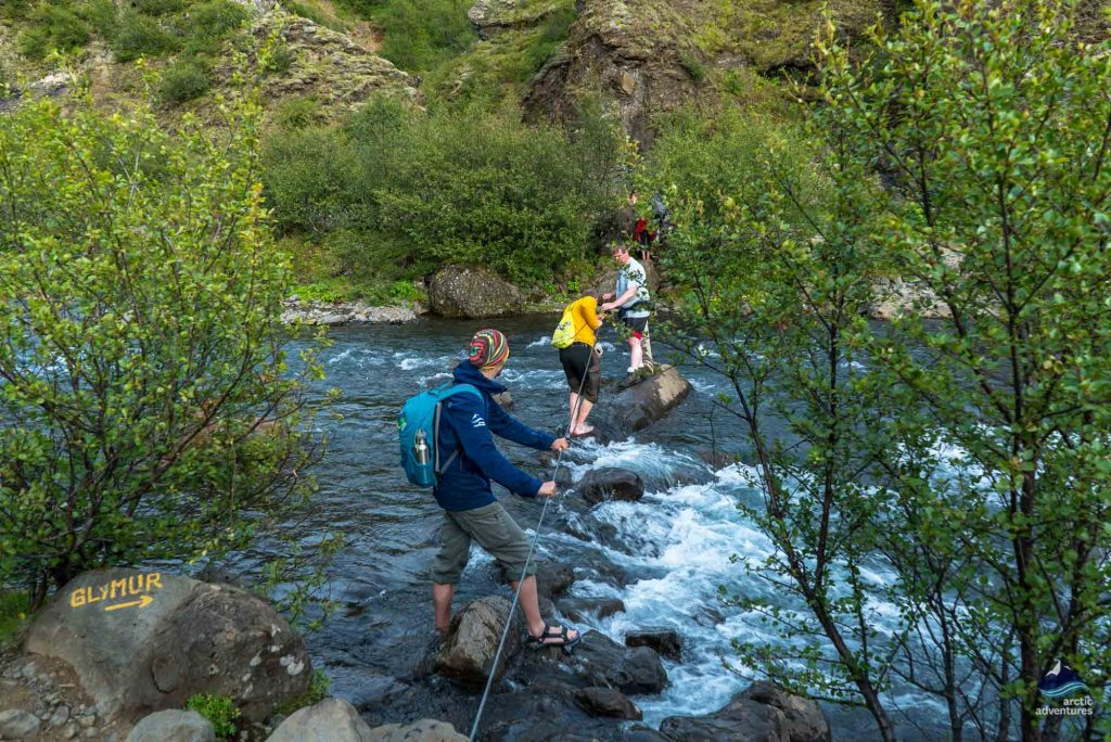 People crossing river near glymur waterfall in Iceland