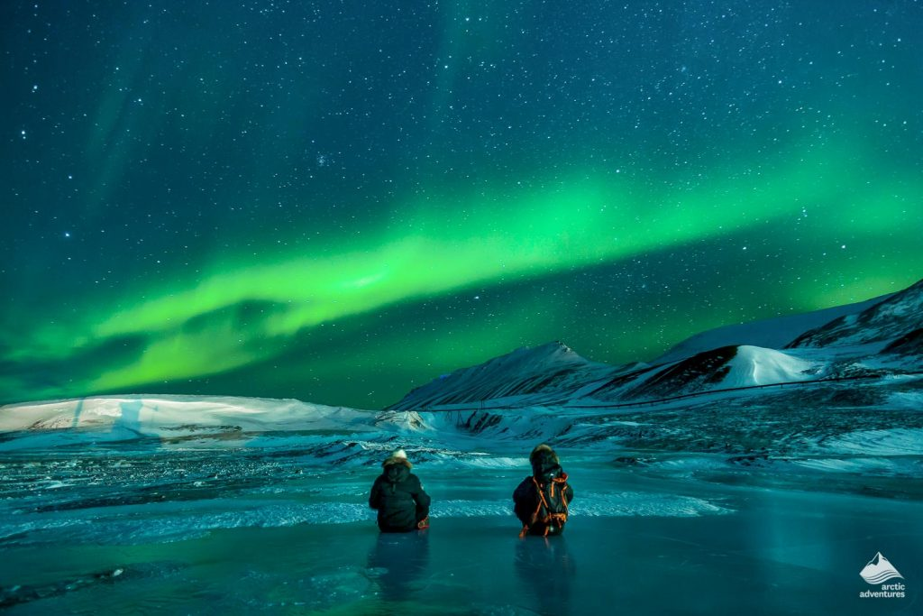 People admiring the Northern Lights on frozen lake