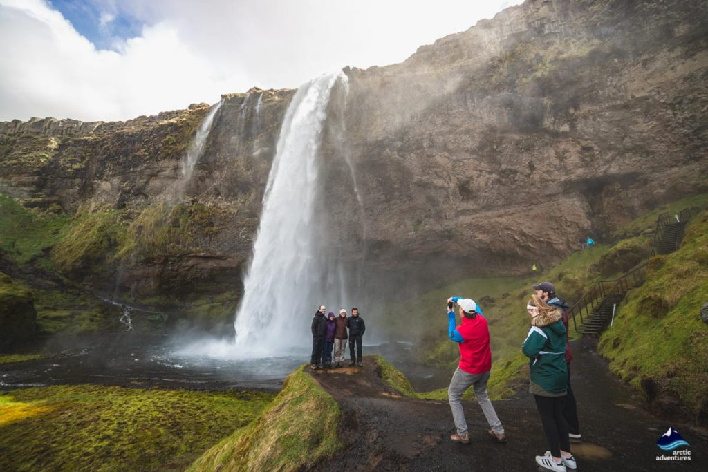 Tourists taking pictures of Seljalandsfoss waterfall